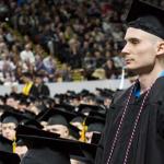 UW graduate standing at ceremony